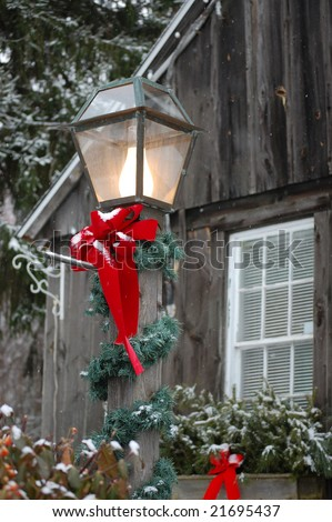Christmas decorations on a rural home with lightly falling snow