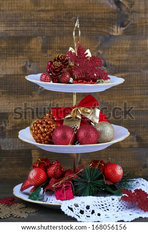 Christmas decorations on dessert stand, on wooden background - stock photo