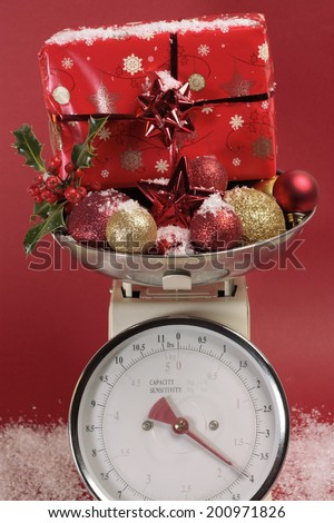 Christmas decorations on weight scale - stock photo