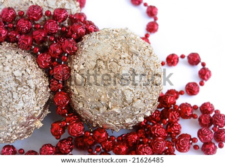 christmas decorations, shiny gold sphere and red garland - stock photo