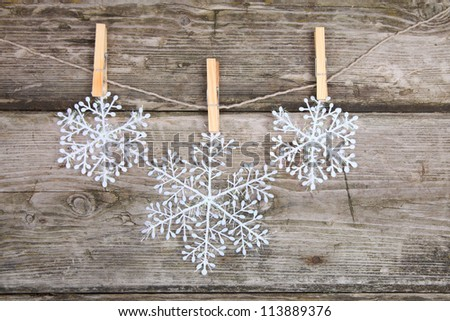Christmas decorations (snowflake) hanging over wooden background - stock photo
