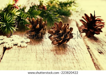 Christmas decorations with fir tree branch, cones on a light wood background. tinting. selective focus on the middle cone