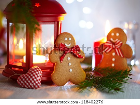 Christmas Decorations with Two Gingerbread men, lamp with candle and christmas baubles - stock photo