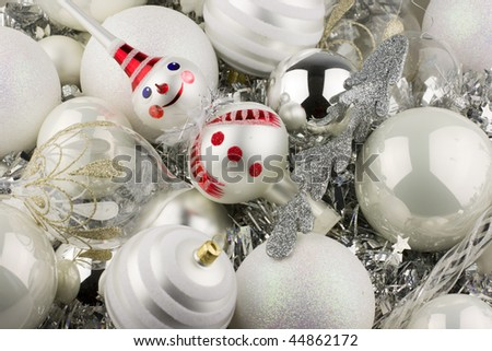 Christmas decorations with white and silver balls, tinsel and a snowman tree topper. - stock photo