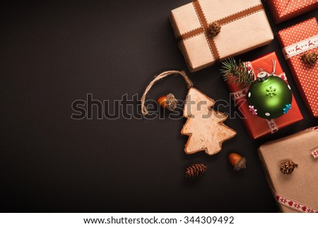 Christmas decorations with wooden tree on black background - stock photo