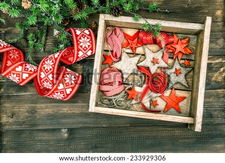 christmas decorations wooden stars and red ribbons with pine tree branches on rustic wooden background. retro style toned picture