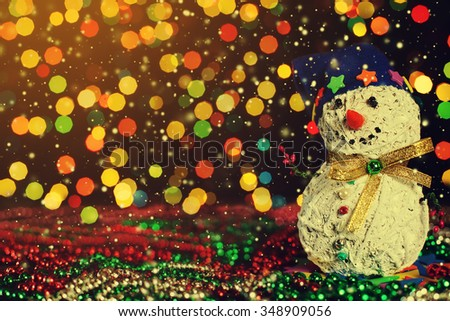 Christmas decorative handmade snowman on the garland lights background.  Magic snowfall in lantern light. Closeup. Selective focus. Copy space  - stock photo