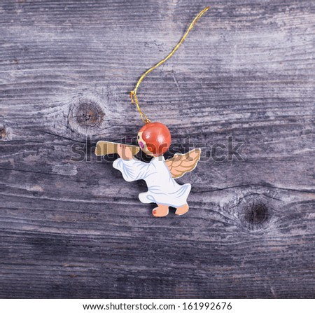 Christmas decorative ornament - Angel with flute on wooden background - stock photo