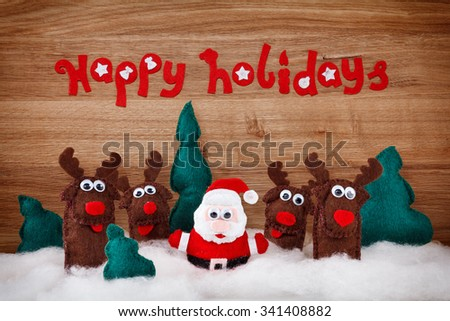 Christmas deer and Santa Claus. The concept of Xmas soft toys made of felt in the snow on a wooden background with the words - Happy Holidays - stock photo