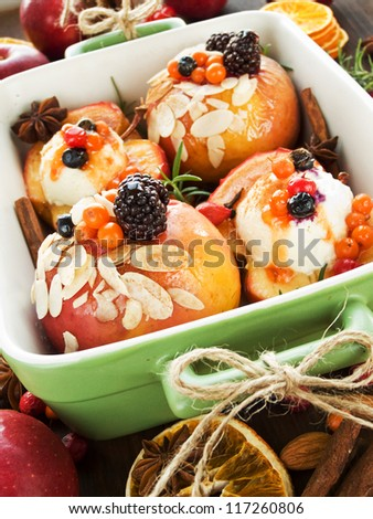 Christmas dessert baked apples with berries, cinnamon and mascarpone. Shallow dof. - stock photo