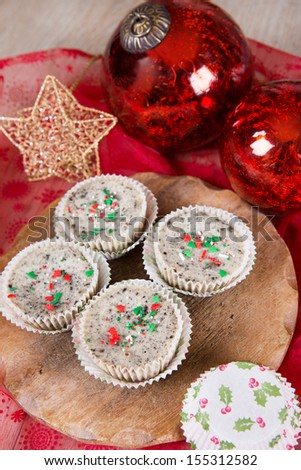 Christmas dessert: Mini cookies and cream cheesecakes in muffin forms with red Christmas tree balls