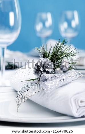 Christmas dinner place setting with silver pinecone decoration napkin with blue background - stock photo