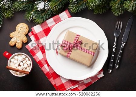 Christmas dinner plate, silverware, fir tree, gift box, hot chocolate. Top view