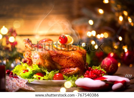 Christmas Dinner. Roasted chicken. Winter Holiday table served, decorated with candles. Roast turkey over wooden background with christmas tree, table setting.