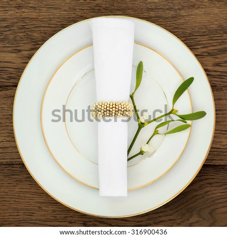 Christmas dinner table setting with plates, napkin and mistletoe over old oak background. - stock photo