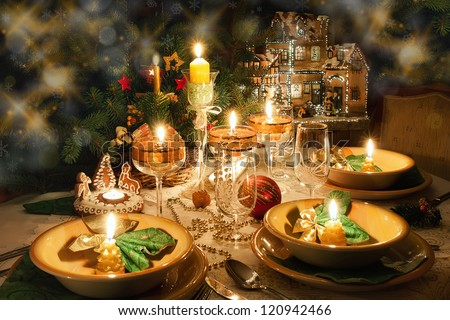 Christmas dinner table with candles with christmas atmosphere - stock photo