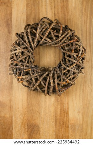 Christmas door wreath brown twigs on sapele wood background, copy space - stock photo