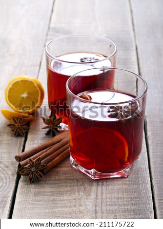 Christmas drink with lemon, star anise and cinnamon sticks in glasses - stock photo