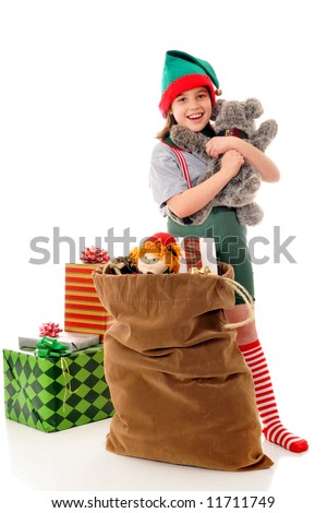 Christmas elf hugging a plush animal before placing into Santa's sack.  Isolated on white.