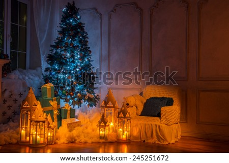 Christmas Eve. Beautiful cozy Christmas interior with high blue fur tree surrounded by burning lanterns, candles and wrapped presents covered with decorative snow - stock photo