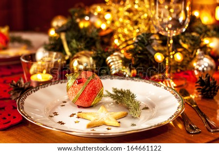 Christmas eve dinner party table setting with lights and gold glittering decorations - elegant white plate close up - stock photo