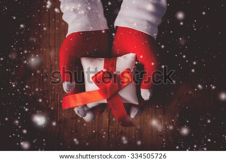 Christmas eve gift, hands giving wrapped present, top view retro toned image with selective focus - stock photo