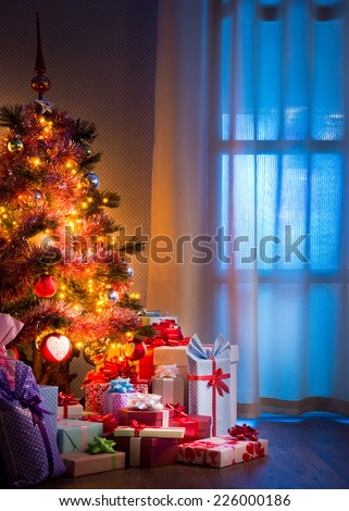 Christmas eve's night with colorful gifts and tree with lights. - stock photo