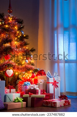 Christmas eve's night with colorful gifts and tree with lights.
