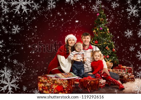 Christmas family of four persons and fir tree with gift boxes over red background - stock photo