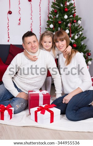 Christmas family portrait in decorated living room with Christmas tree - stock photo