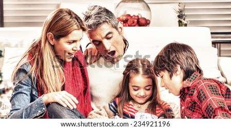 Christmas family scene. Daughter opening gift with parents and brother surprise. - stock photo