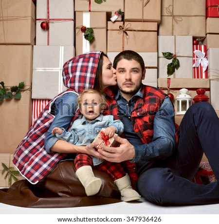 Christmas Family with baby toddler Kid on rustic craft presents gift wall. Happy Parents hugging kissing Child at Home Celebrating New Year. Christmas scene - stock photo