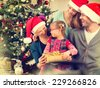Christmas Family with Kids opening Christmas gifts. Happy Smiling Parents and Children at Home Celebrating New Year. Christmas Tree. Christmas scene - stock photo