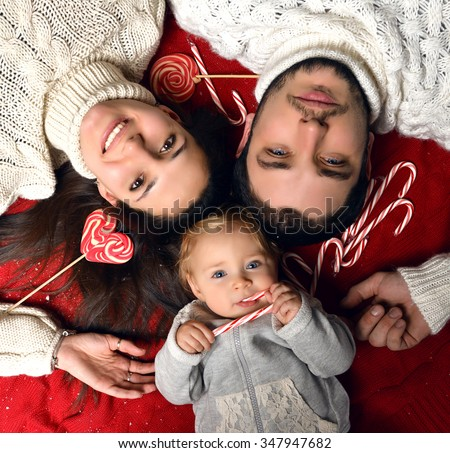 Christmas Family with small baby infant Kid lying on the floor. Happy young Parents and Child at Home Celebrating New Year with candies - stock photo