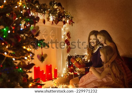 Christmas Family Woman Portrait, Mother And Daughters Celebrate Holiday, Opening Present Gift Box In Room Decorated By Xmas Tree and Candles Lights - stock photo