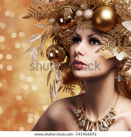 Christmas Fashion Girl with Decorated Hairstyle. Portrait of Beautiful Young Woman with Gold Christmas Balls