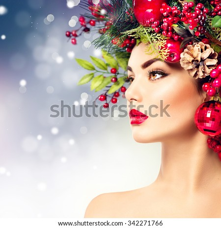 Christmas fashion model woman. Xmas New Year hairstyle and make up. Beauty Girl portrait. Gorgeous Vogue style Lady with Christmas decorations on her head, baubles, professional makeup, red lipstick - stock photo