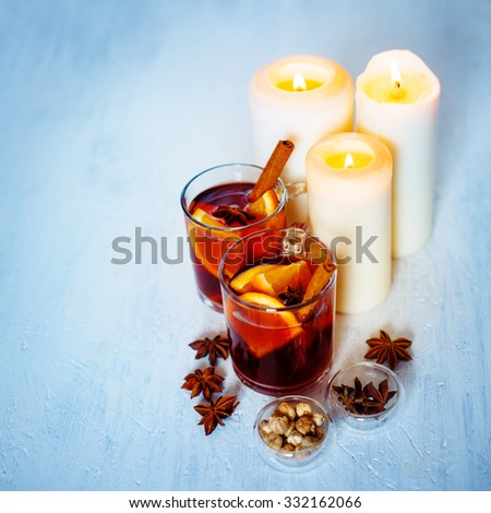 Christmas Festive Mood. Two Glasses with Mulled Wine, Spices and White Candles. Selective Focus, Shallow DOF. - stock photo