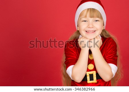Christmas fever. Horizontal portrait of a little adorable girl in Christmas outfit posing in studio against red background  - stock photo