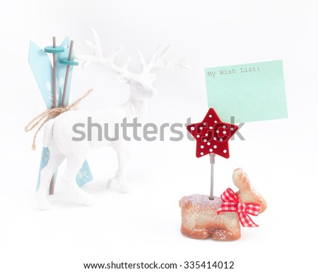 Christmas figurines; in front and in focus is rabbit with Christmas star and attached wish list; reindeer with skis is blurred in background - stock photo