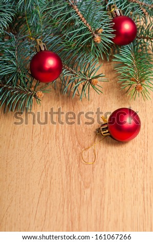 Christmas fir and red balls on wooden background