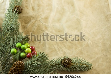 Christmas fir branch with pinecone and berry accent on antique style paper and copyspace - stock photo