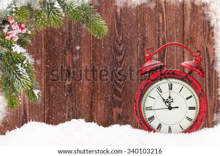 Christmas fir tree and alarm clock in snow - stock photo