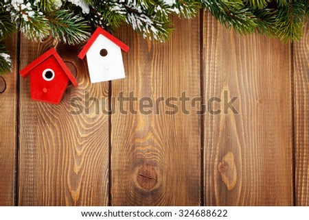 Christmas fir tree and birdhouse decor on rustic wooden board with copy space - stock photo