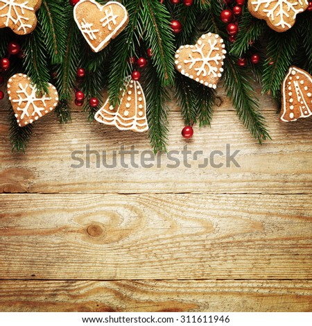 Christmas fir tree and cookies on wooden board background with copy space