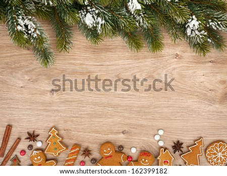 Christmas fir tree and gingerbread cookies on wooden board - stock photo