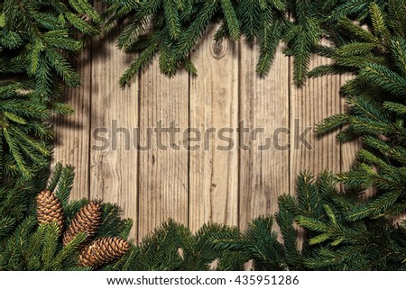 Christmas fir tree branch decorations with cone on wooden background - stock photo