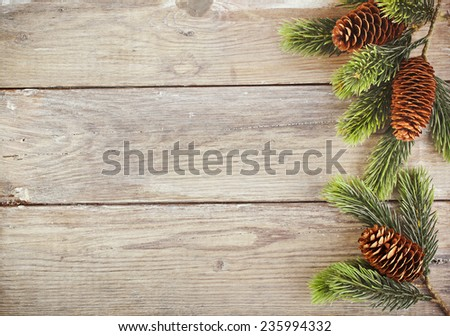 Christmas fir tree branch on old wooden surface for your text - stock photo