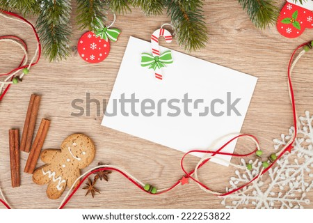 Christmas fir tree, gingerbread cookies and card for copy space on wooden table - stock photo