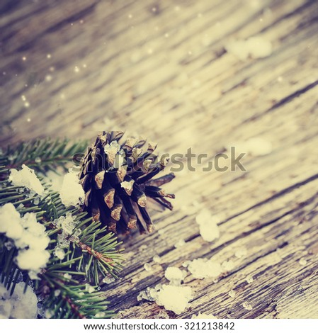 Christmas fir tree with cones and snow on a wooden background, selective focus - stock photo